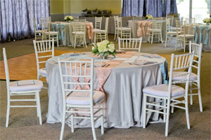Photo of an event setup with tables and chairs