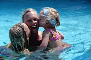 Image of two young girls kissing their mother in a pool